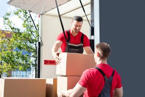 Two male removalists unloading in a van and passing boxes