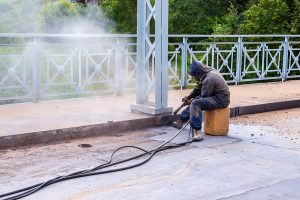 Worker with protective mask while performing mobile sand blasting