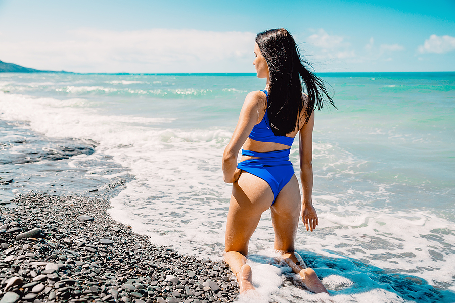 Woman wearing a blue high waisted thong bikini